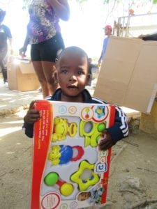 little boy holding toy at toy drive
