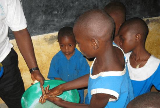 children washing hands in bucket