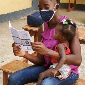 Haiti Mom Baby with MFH COVID Pamphlet cropped