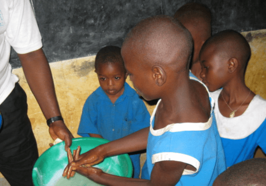 children washing hands in bucket